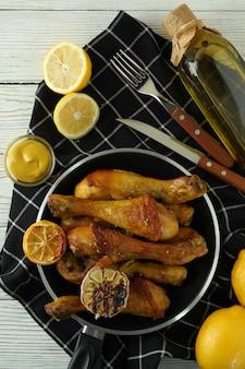 Concept van heerlijk eten met pan van gebraden kip drumsticks op witte houten tafel