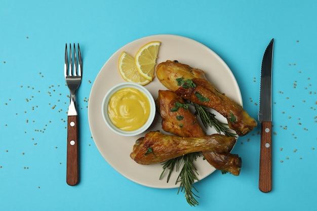 Concept van heerlijk eten met plaat van gebraden kip drumsticks op blauwe achtergrond
