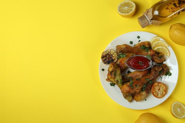 Concept van heerlijk eten met plaat van gebraden kip drumsticks op gele achtergrond