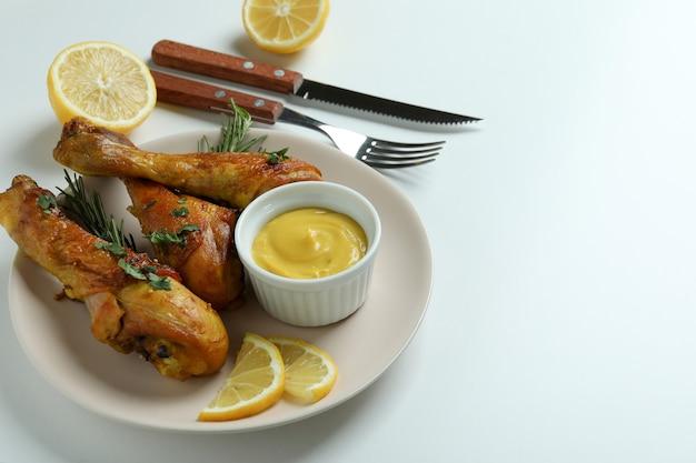 Concept van heerlijk eten met plaat van gebraden kip drumsticks op witte achtergrond