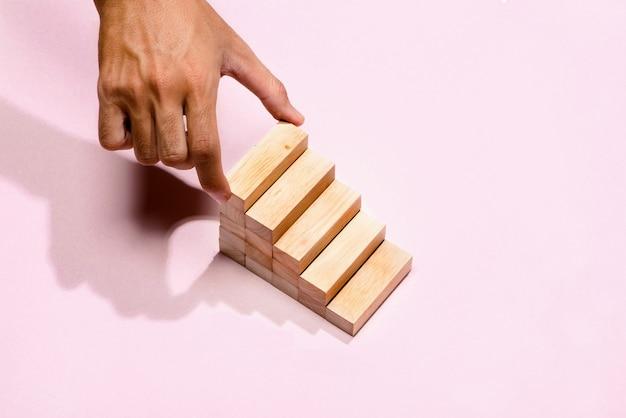 Concept van het bouwen van successtichting. mannenhand zet houten blokken in de vorm van een trap