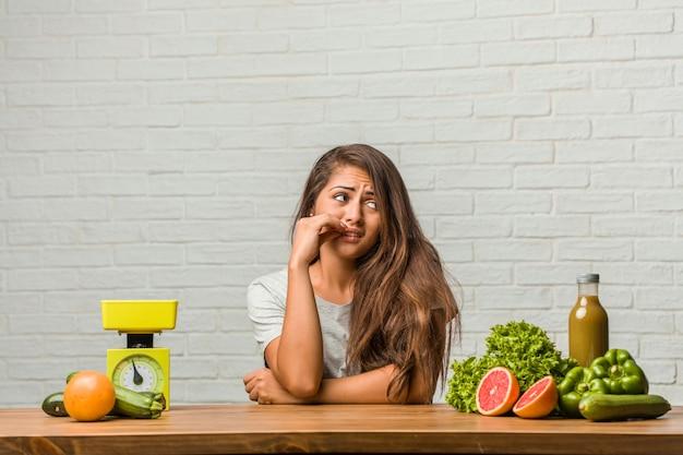 Concept van het dieet. portret van een gezonde jonge latijns-vrouw die bijt, nerveus en erg angstig en bang voor de toekomst, voelt paniek en stress