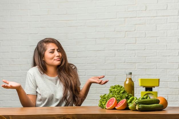 Concept van het dieet. portret van een gezonde jonge latijns-vrouw twijfelen en schouders ophalen