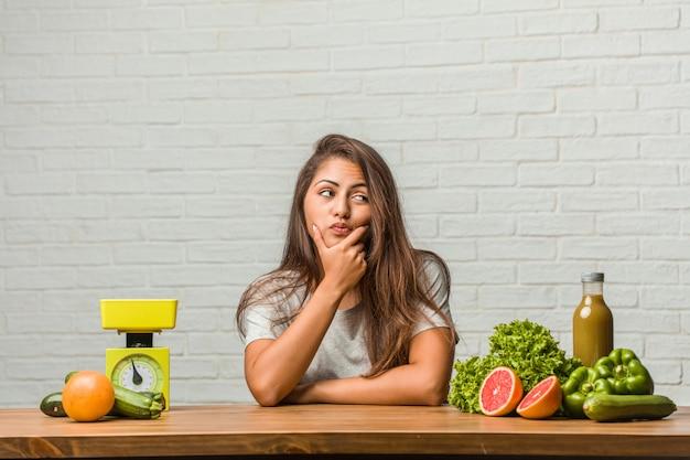 Concept van het dieet. portret van een gezonde jonge latijns-vrouw twijfelen en verward