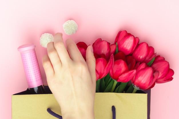 Concept van het geschenk met wijn en rode tulpen in de papieren zak op de roze achtergrond. plat leggen, ruimte kopiëren. de vrouwenhand neemt snoepjes van de huidige zak tot vrouwendag, moederdag, de lenteconcept