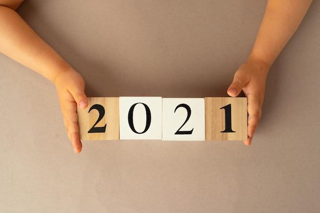 Concept van het jaar 2021 met handen met houten kubussen
