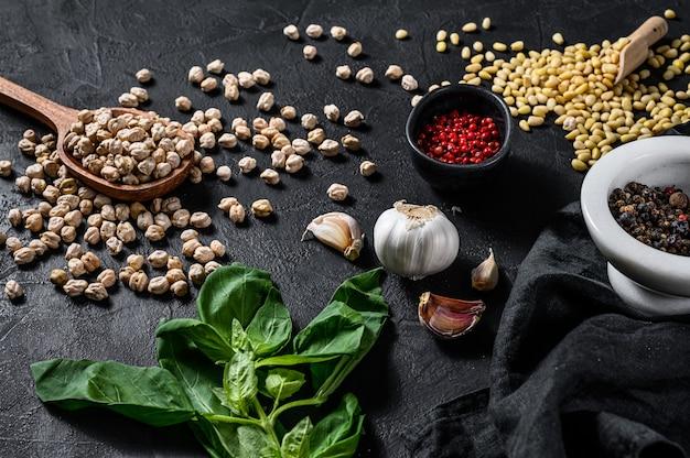 Concept van het koken van humus. ingrediënten: knoflook, kikkererwten, pijnboompitten, basilicum, peper. zwarte achtergrond. bovenaanzicht