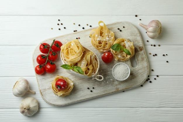 Concept van het koken van smakelijke pasta op witte houten tafel