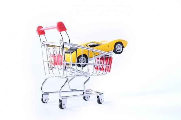 Concept van het kopen van een nieuwe auto. stuk speelgoed auto in geïsoleerde boodschappenmand