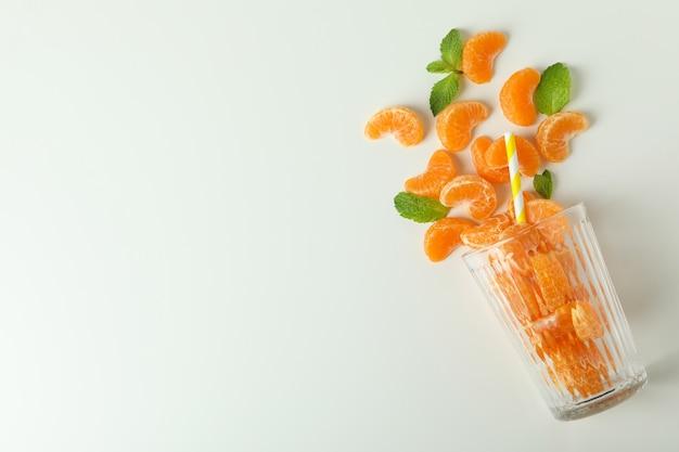 Concept van het maken van mandarijnensap met glas met mandarijnen op witte achtergrond.