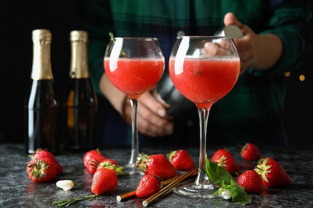 Concept van het maken van rossini-cocktails tegen een donkere achtergrond