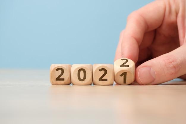 Concept van het met de hand veranderen van het jaar van 2021 naar 2022 op houten kubussen.