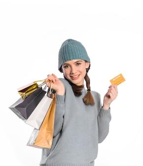 Concept van het moderne leven, de consumptiemaatschappij, snelle mode, winkelen en verkoop. jonge vrouw met boodschappentassen en creditcard.