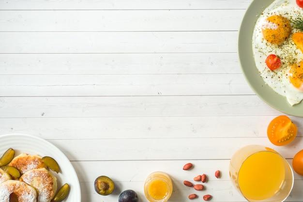 Concept van het ontbijt. gebakken eieren, kwarkpannekoeken, pruimen en havermout met melk, jus d'orange op tafel