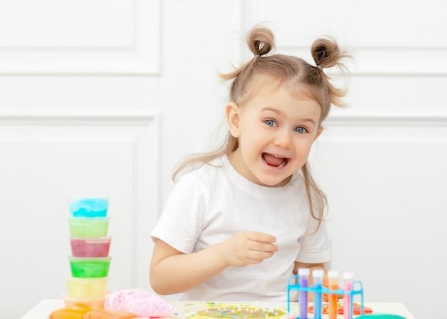 Concept van het ontwikkelen van kindervaardigheden en leren. wetenschapper jongen plezier maken van slijm in het laboratorium