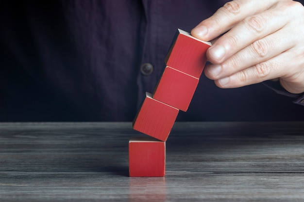 Concept van het overwinnen van de crisis. hand houdt de vallende toren van kubussen.