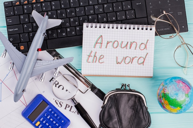 Concept van het plannen van vakantie - vliegtuig, wereldbol, portemonnee. over de hele wereld geschreven op het kladblok.