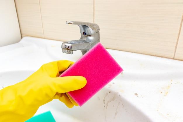Concept van het reinigen van oude vuile wastafel met roestvlekken, kalk en zeep vlekken in de badkamer