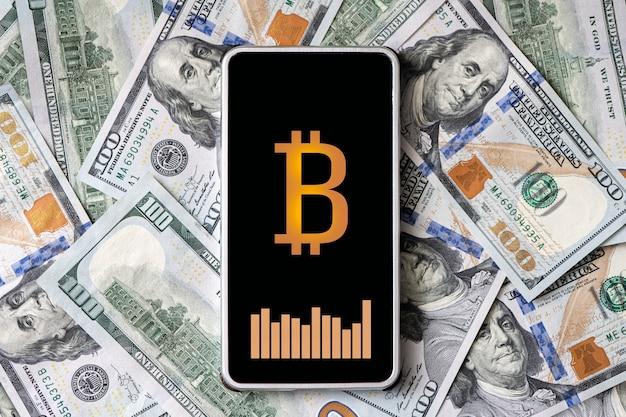 Concept van het verdienen van geld op cryptocurrency. een smartphone met een bitcoin-logo en een wisselkoersgrafiek op het smartphonescherm tegen de achtergrond van geld. alle afbeeldingen zijn verzonnen.