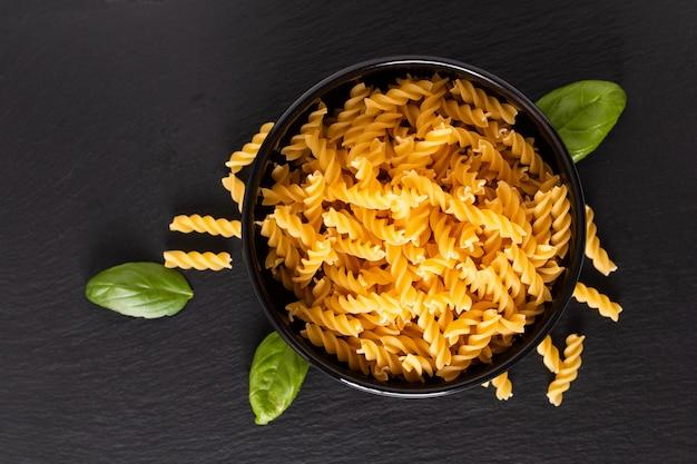 Concept van het voedsel de ruwe organische italiaanse fusili-deegwaren in zwarte kom op zwarte leiraad met exemplaarruimte