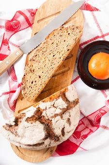 Concept van het voedsel het organische franse zuurdesem op houten scherpe raad