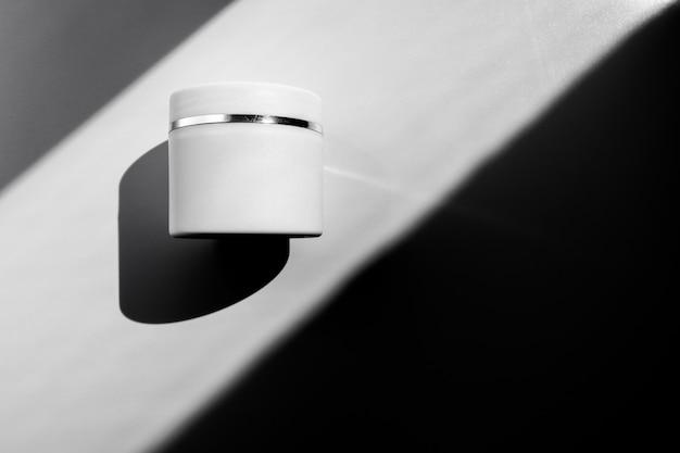 Concept van huidverzorging. witte plastic pot met vochtinbrengende lichaams- of gezichtscrème in direct zonlicht op een witte achtergrond.