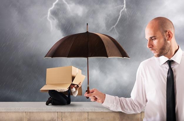 Concept van hulp in uw bedrijf met een grote zakenman die een paraplu vasthoudt
