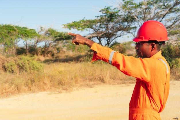 Concept van ingenieur of technicus. afrikaanse mannelijke monteur in oranje uniform en wijzende vinger.