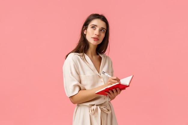 Concept van inspiratie, creativiteit en onderwijs. geconcentreerd peinzend en creatief jong meisje dat verbeelding gebruikt en denkt omhoog te kijken, vroeg zich af om even te stoppen als iets in een rood notitieboekje te schrijven