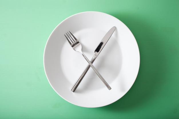 Concept van intermitterend vasten en ketogeen dieet, gewichtsverlies. vork en mes gekruist op een bord