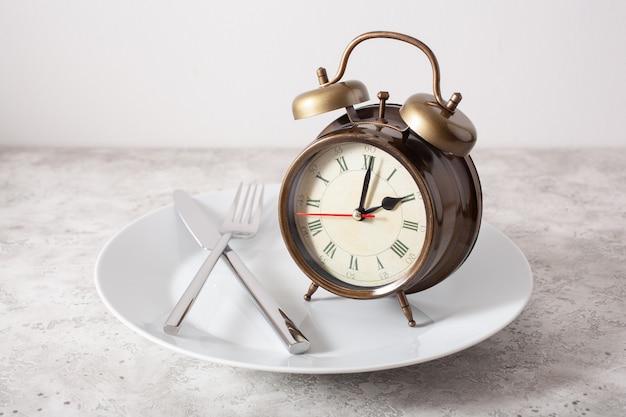 Concept van intermitterend vasten, ketogeen dieet, gewichtsverlies. vork en mes gekruist en wekker op plaat