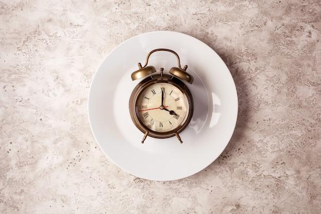 Concept van intermitterend vasten, ketogeen dieet, gewichtsverlies. wekker op plaat