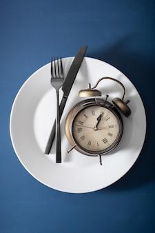 Concept van intermitterend vasten, ketogeen dieet, gewichtsverlies. wekker vork en mes op een plaat