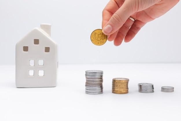 Concept van investering in onroerend goed hand zetten munt met witte huis op achtergrond lening nemen