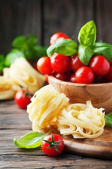 Concept van italiaans eten met pasta, basilicum en tomaat, selectieve aandacht