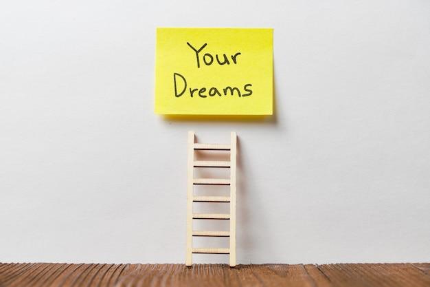 Concept van je dromen geschreven op een sticker onder de trap.