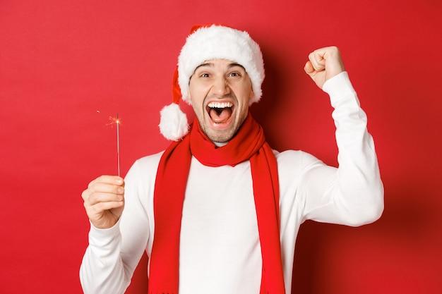 Concept van kerst wintervakantie en viering portret van opgewonden knappe man die hand opsteekt...