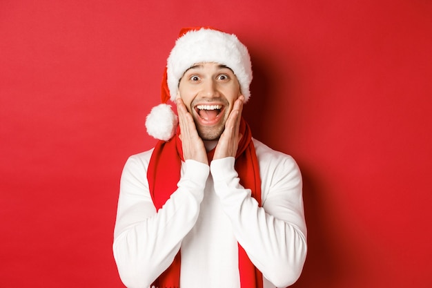 Concept van kerstmis, wintervakantie en feest. close-up van een verraste en gelukkige man in kerstmuts en sjaal, kijkend naar iets geweldigs, staande over rode achtergrond.