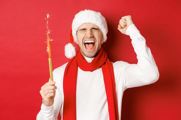 Concept van kerstmis, wintervakantie en feest. knappe man die nieuwjaar viert en plezier heeft, een sterretje vasthoudt en glimlacht, een kerstmuts draagt, over een rode achtergrond staat