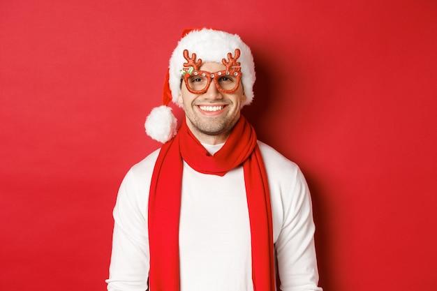 Concept van kerstmis, wintervakantie en feest. vrolijke knappe kerel in nieuwjaarsfeestbril en glimlachend, staande over rode achtergrond