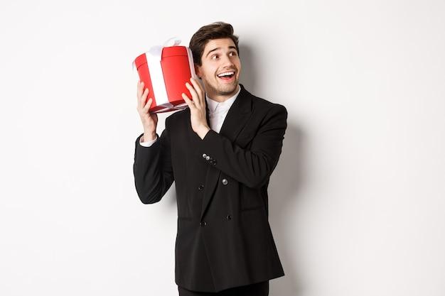 Concept van kerstvakantie, feest en levensstijl. afbeelding van aantrekkelijke man in zwart pak, cadeau schuddend om te raden wat erin zit, genietend van het nieuwe jaar, staande tegen een witte achtergrond.