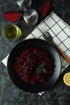 Concept van lekker eten met bietensalade op zwarte rokerige tafel