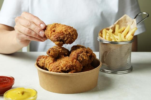 Concept van lekker eten met gebakken kip op witte getextureerde tafel