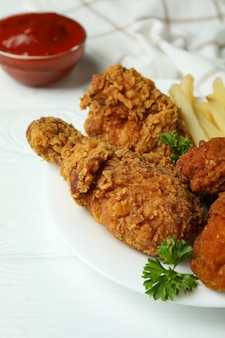 Concept van lekker eten met gebakken kip op witte houten achtergrond