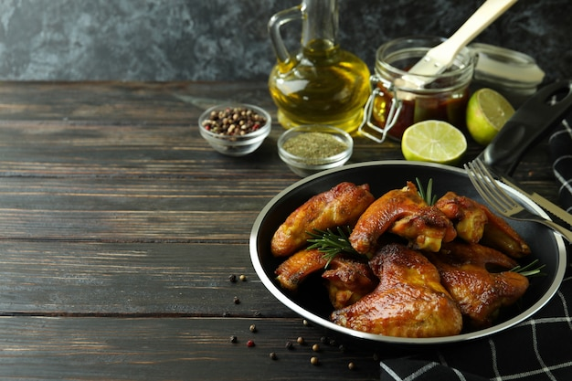 Concept van lekker eten met gebakken kippenvleugels op houten achtergrond, ruimte voor tekst