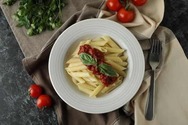Concept van lekker eten met pasta met tomatensaus op zwarte smokey tafel