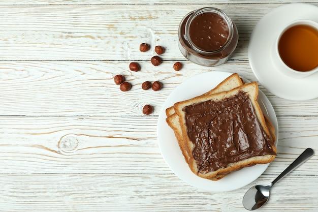 Concept van lekker ontbijt met chocoladepasta op witte houten tafel