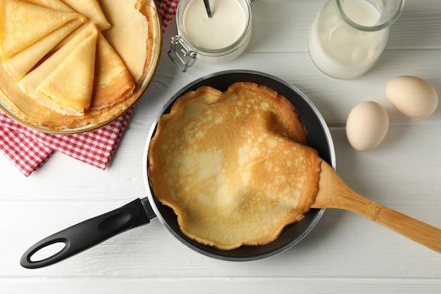 Concept van lekker ontbijt met dunne pannenkoeken op witte houten tafel