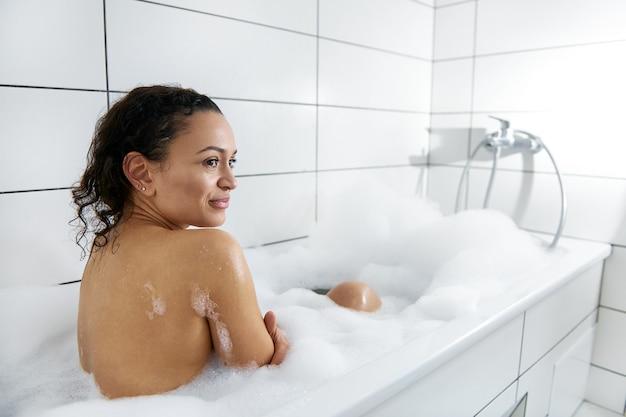 Concept van lichaamsverzorging en genot thuis. zijaanzicht van een jonge vrouw die een bubbelbad met schuim thuis neemt