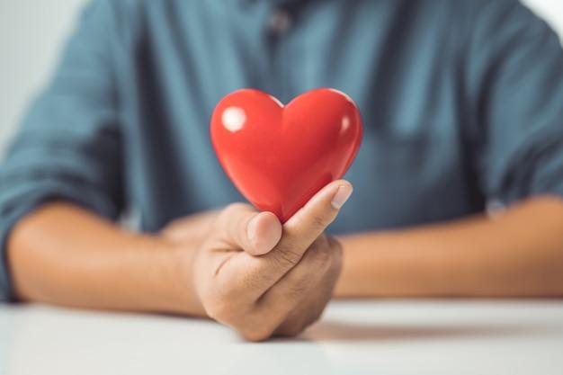 Concept van liefde mannelijke handen met rood hart werelddag voor geestelijke gezondheid levens- en ziektekostenverzekering
